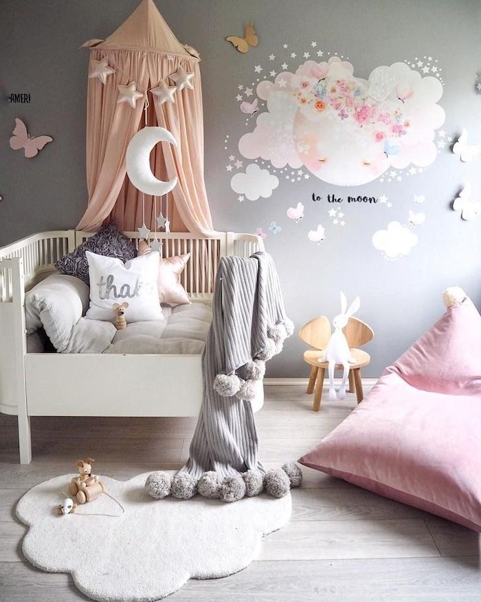 chambre bébé fille déco avec lit blanc à barreaux tapis doux blanc coussin d assise rose mur gris clar sur parquet bois clair coussins décoratifs