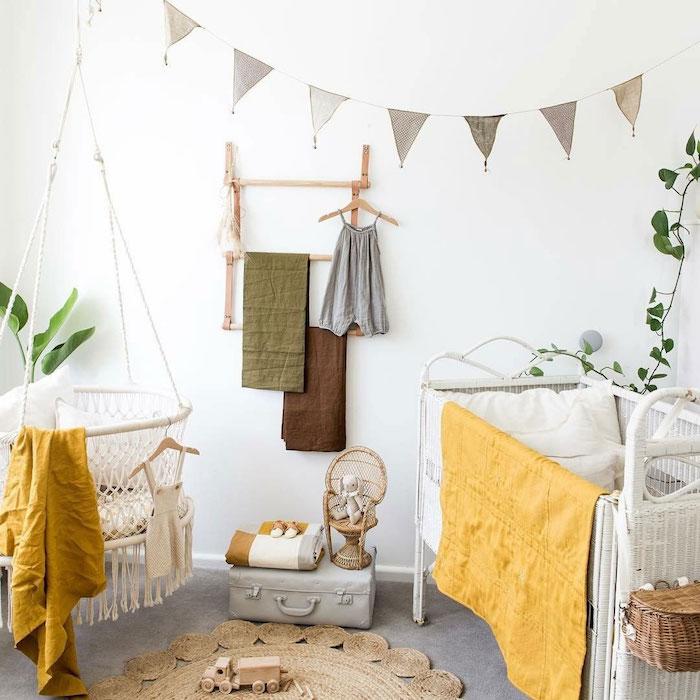 chambre bébé mixte décoré aux accents jaunes fauteuil suspendu blanc lit blanc metallique tapis rond vetements enfant suspendus sur des patères