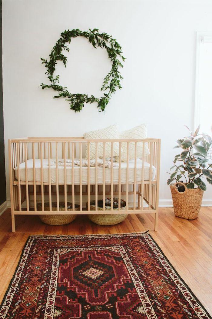 chambre bébé nature avec lit bois coussins blancs tressés paniers de rangement tressés plante verte en panier tapis cosy sur parquet bois clair