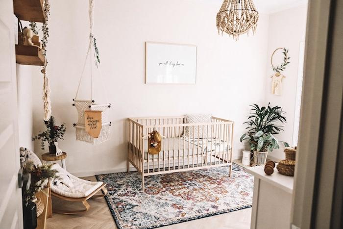 chambre cocooning fille bébé tapis coloré berceau bois lit barreaux balancoire macramé plantes vertes murs blancs parquet bois clair