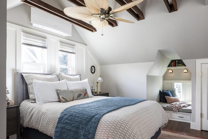 chambre mansardée ventilateur de plafond poutres apparentes bois foncé nid cocooning sous fenêtre coussins décoratifs