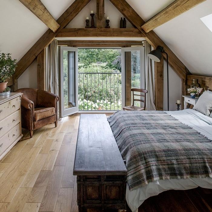 chambre parentale cosy style rustique déco blanc et bois fauteuil cuir marron banquette bois brut lampe sur pied noir mat