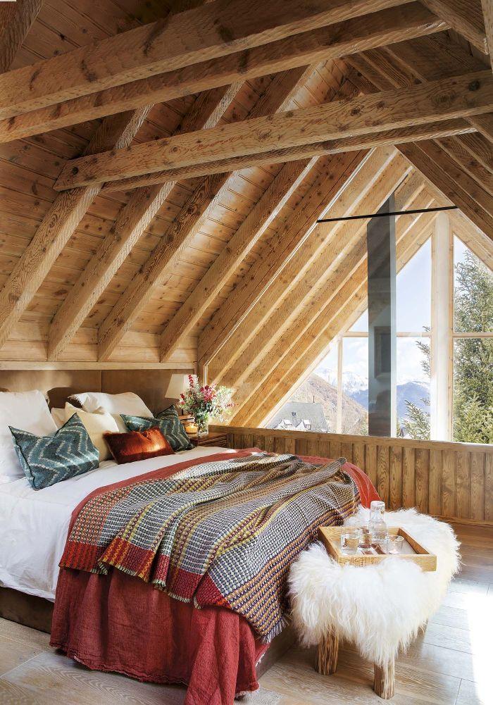 chambre sous comble mansardée deco rustique avec des couvertures chades bout de lit couvert de peau de mouton parquet bois clair