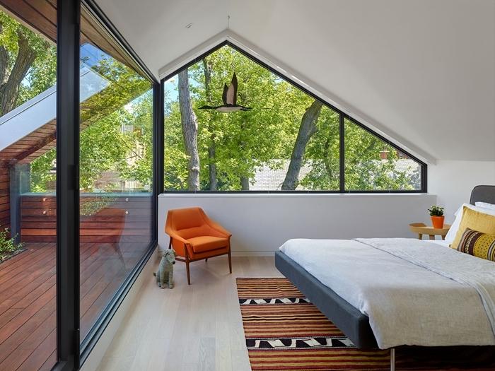 chambre sous pente style moderne porte coullisante balcon terrasse bois tapis orange et noir fauteuil orange