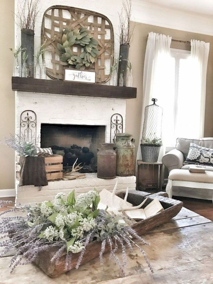 cheminée bois et briques blanchies table basse bois avc deco florale canapé gris deco vintage chic accents decoratifs