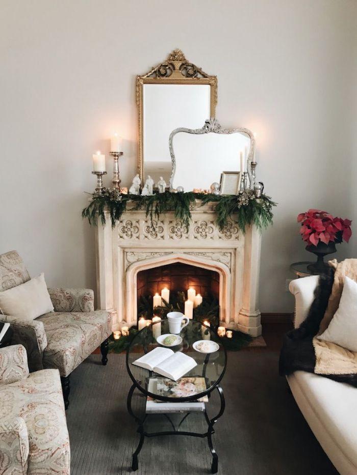 cheminée vintage blanche décorée de branches de pin fauteuils à motifs canapé blanc table basse en verre et métal miroirs vintage