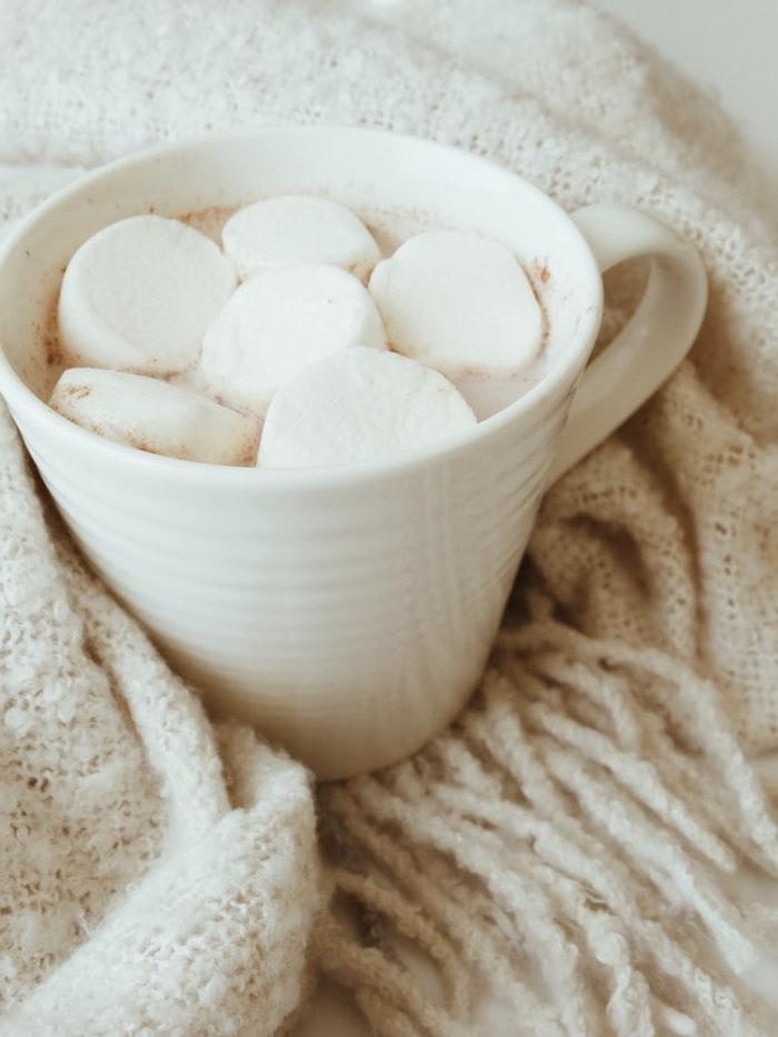 chocolat chaud blanc aux guimauves dans tasse blanche et couverture douillette idée boisson noel