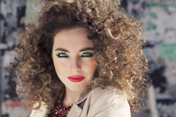 coiffure disco jeune femmes avec cheveux boucles maquillage années 80 fards vertes et rouge a levres devant un mur aux graffiti