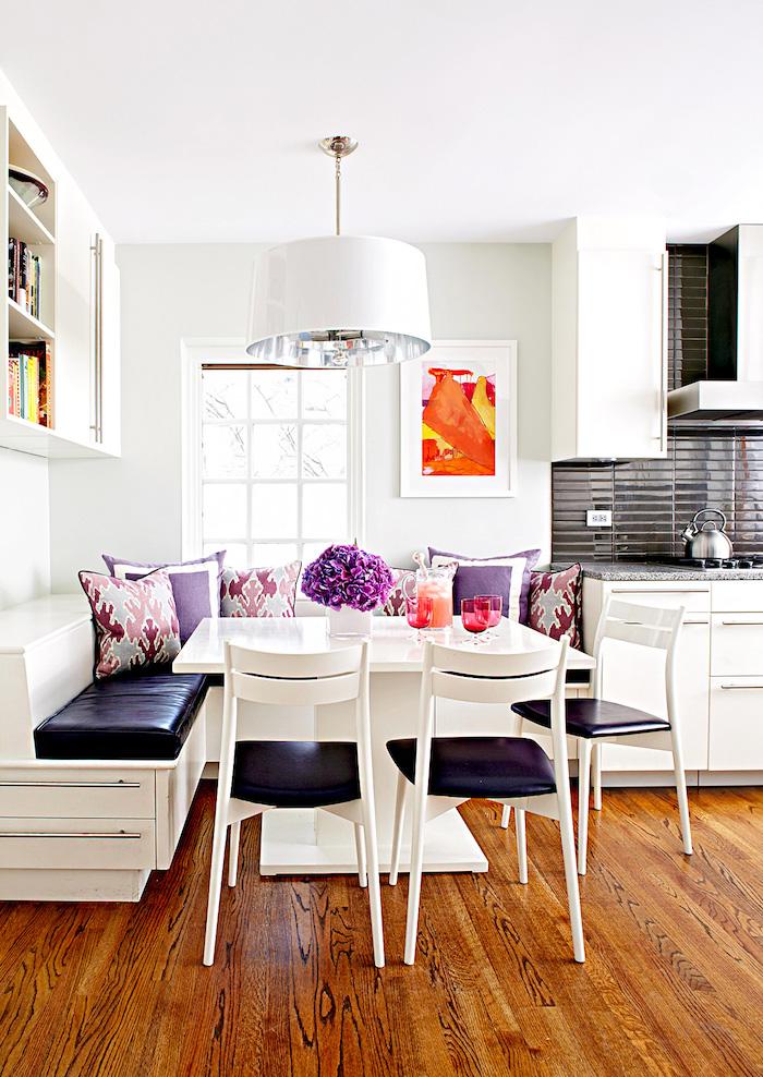 coin de repas cuisine avec une banquette table et chaises blancs parquet sur le sol et murs blancs