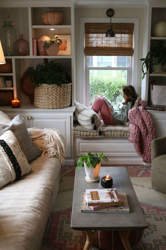 coin lecture coté fenetre avec coussins d assise table basse bois canapé blanc cassé tapis original etageres décorés de déco rustique chic