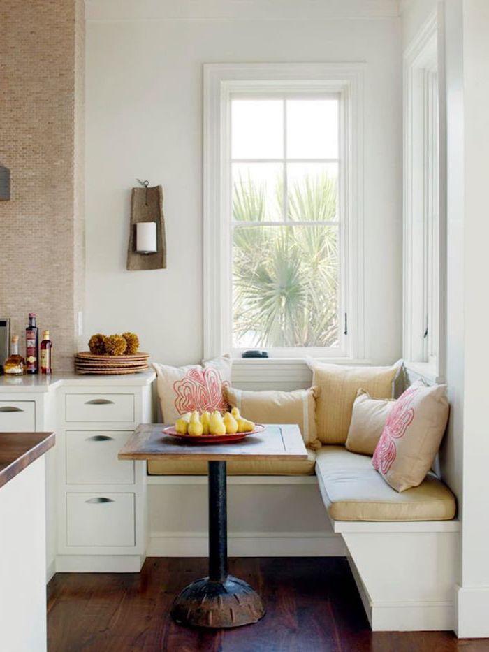 coin repas d angle avec un banc et petite table meubles blanches et sol fonce une fenetre qui donne vers le jardin