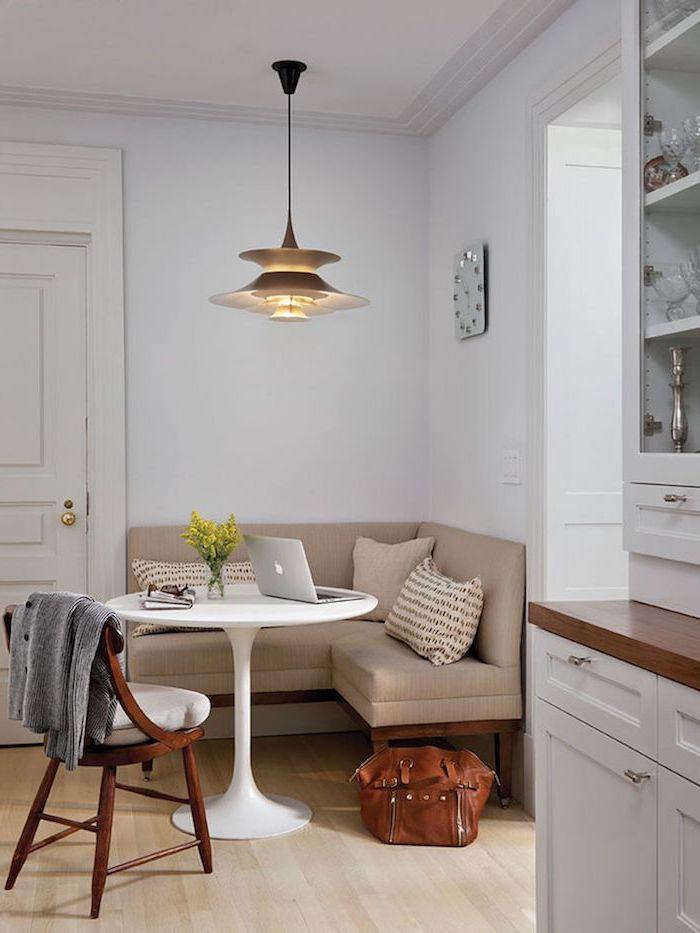 coin repas d angle avec un canape beige des placards en bois et table blanche avec ordinateur portable