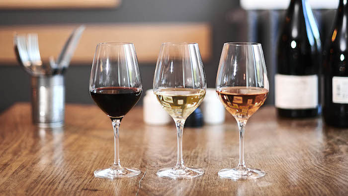 coment deguster et servir du vin trois verres a tige avec vin blanc rouge et rose sur une table en bois