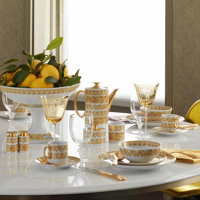 comment dresser une table avec des assiettes en porcelaine ornes des elements en or et un bol plein de citrons avec des nappes jaunes