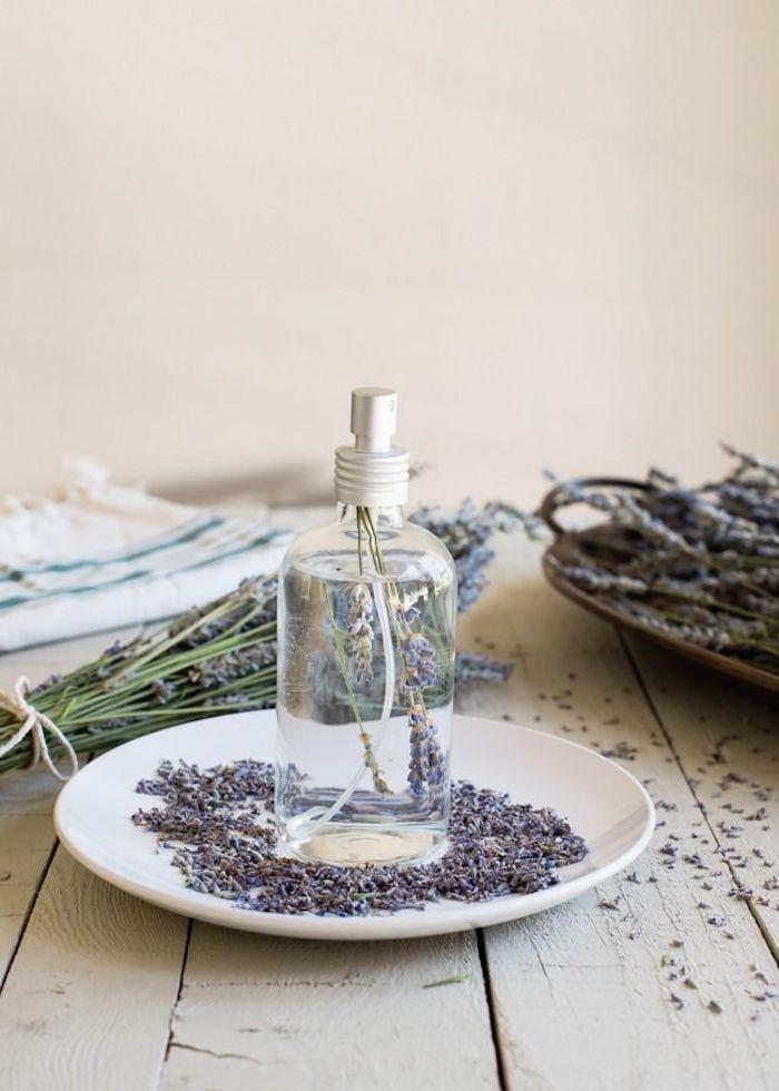 comment faire de l eau de lavande un vaporisateur dans assiette avec des fleurs de lavande sur table en bois