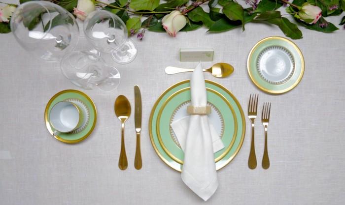 comment placer les couverts poiur un diner avec des couverts dores des assiettes bleus ornes et un bouquet de roses