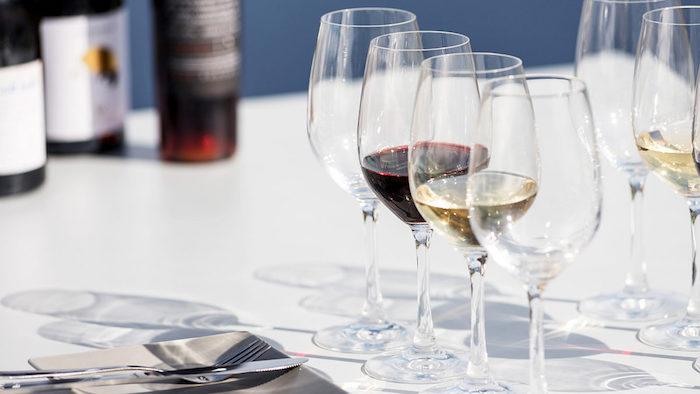 comment places les verres sur une table verres de vin rouge et blanc a cote de couverts et bouteilles de vin