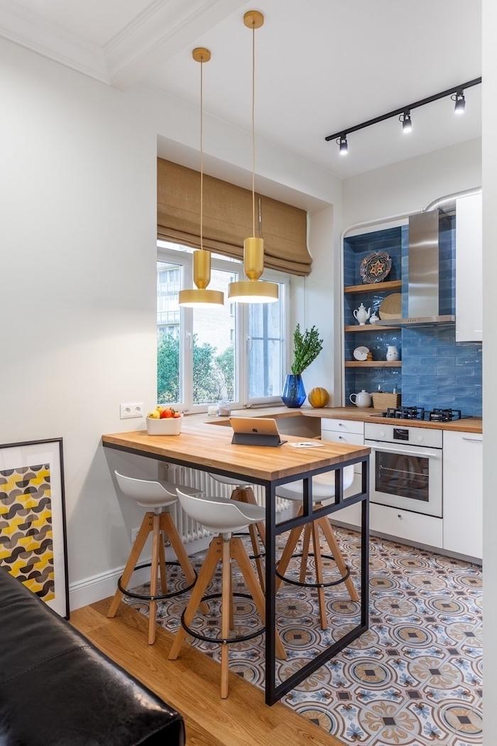 cuisine avec ilot central integre carrelage bleu au dessus des plaques et multicolore au sol chaises de bar autour d une table