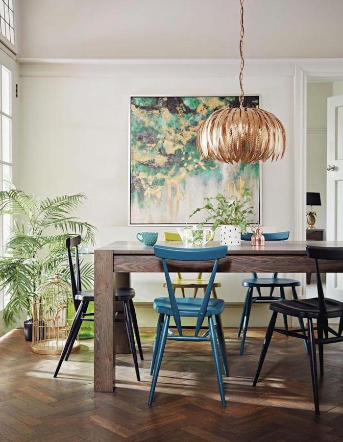 cuisine ouverte bar avec une grande table en bos et chaises metaux a cote d une abondance de palntes vertes