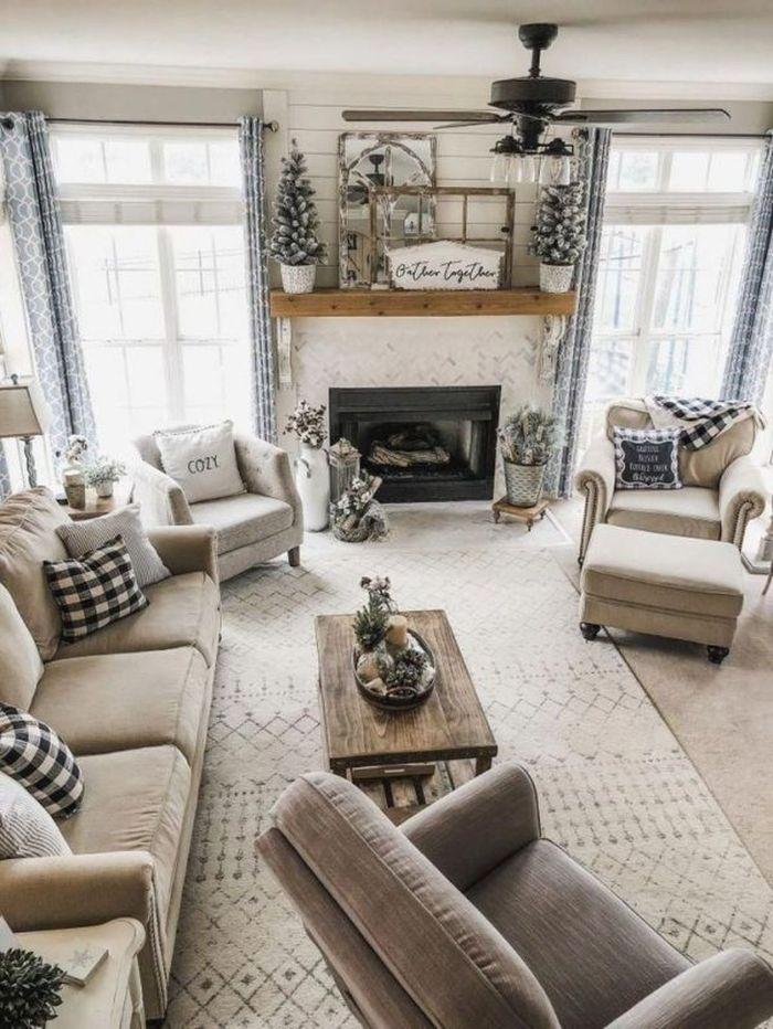 deco blanc et gris perle avec canapés et fauteuils gris table basse bois brut cheminée rusitque lambris mural pins et plaids et coussins cosy