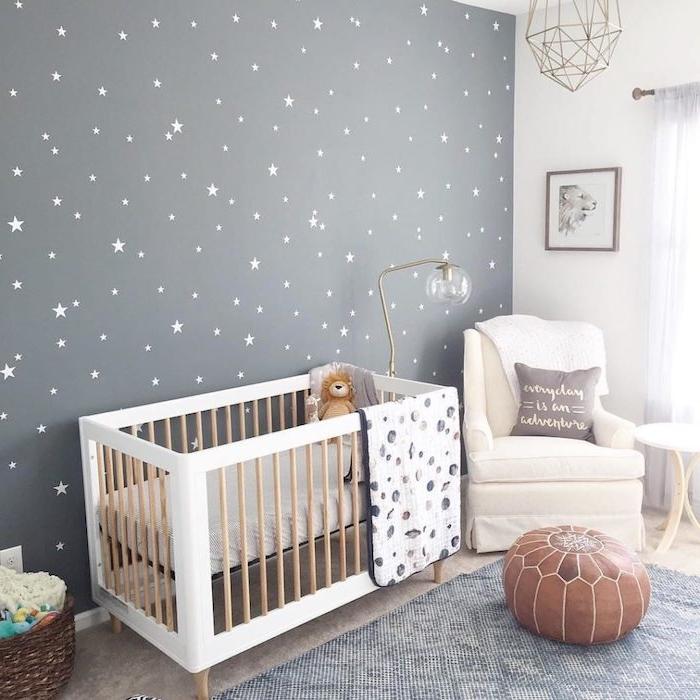 deco chambre bebe mixte lit blanc et bois fauteuil blanc mur gris motif étoiles tapis gris pouf marron rideaux transparentes