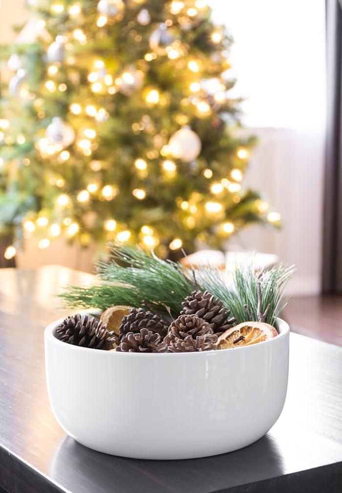 deco noel a fabriquer pot pourri pommes de pin oranges séchés et des brins de pin dans un bol blanc pour decorer une table