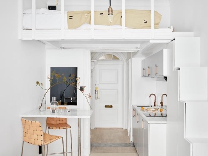 deco petit appartement en blanc et bois carrelage pierre robinet rose gold armoires blanches îlot bar mezzanine lit