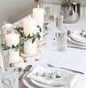 deco table anniversaire avec des branches vertes et fleurs dans assiette verres de champagne et d eaux cristaux