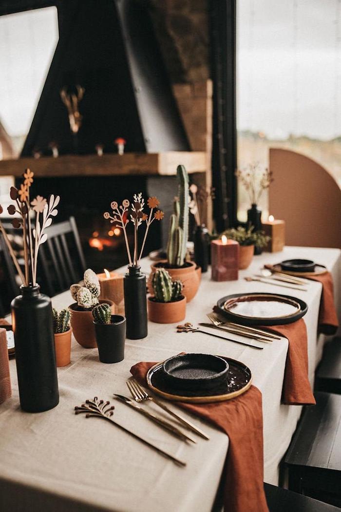 decoration de table originale avec des couverts et vases noirs des pots de cactus et nappes oranges une cheminee au fond de la piece