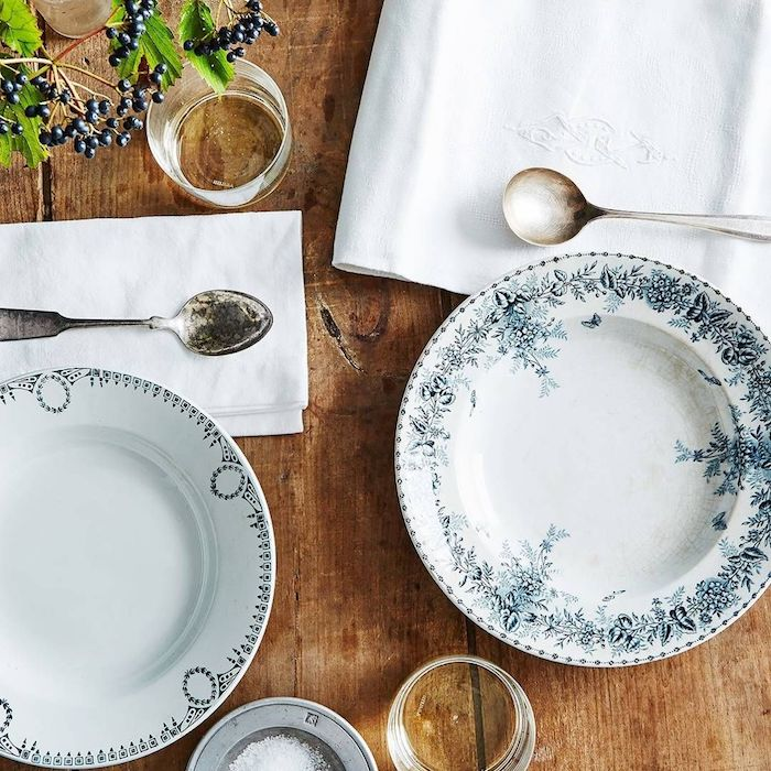 des assiettes de porcelaine bleu et blanc avec des ornament sur une table en bois des nappes avec des monogrammes et une branche de sureau comme decoration