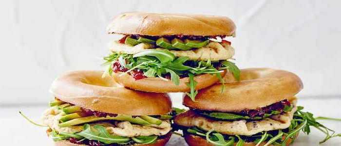 des sandwiches de bagels coupes en deux avec de la viande frommage et roauette que mettre dans un brunch idée de brunch maison