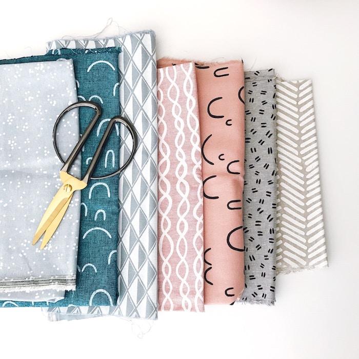 des tissus et un ciseau poses sur la table comment customiser un vetement apprendre a coudre