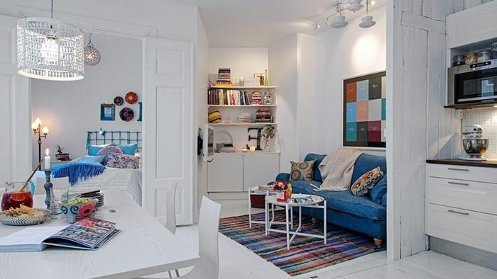 design intérieur studio étudiant décoration canapé bleu table à manger blanche kitchenette studio blanc plan de travail bois foncé