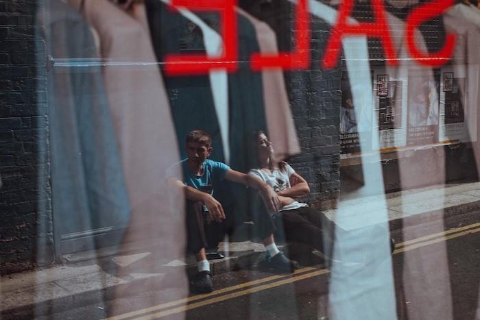 deux gens devant la vitrine d un magasin qui offre des rabais affaire de black friday