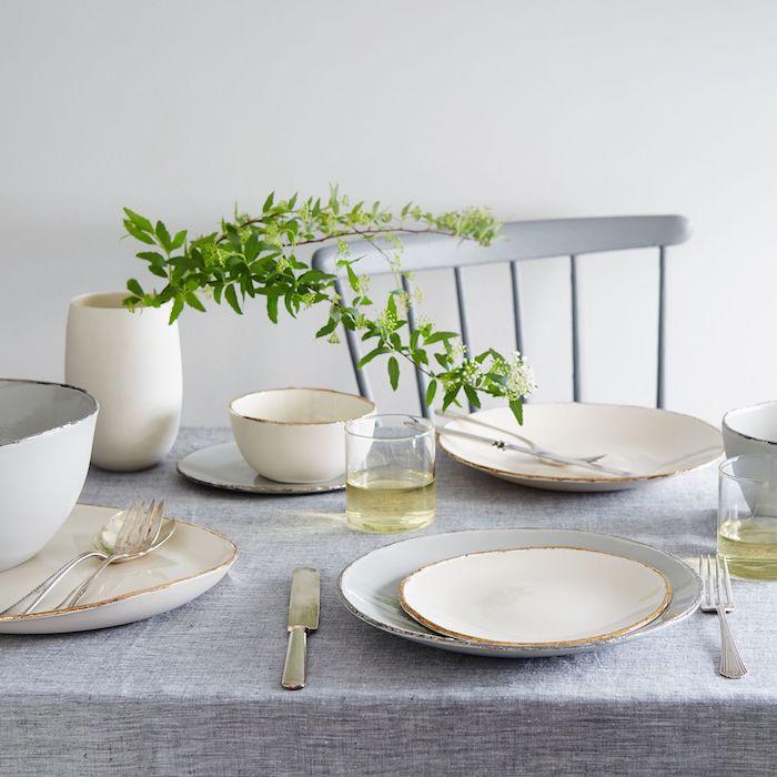 disposition couverts table francaise nappe gris avec des assiettes blanches et des verres avec vin blanc