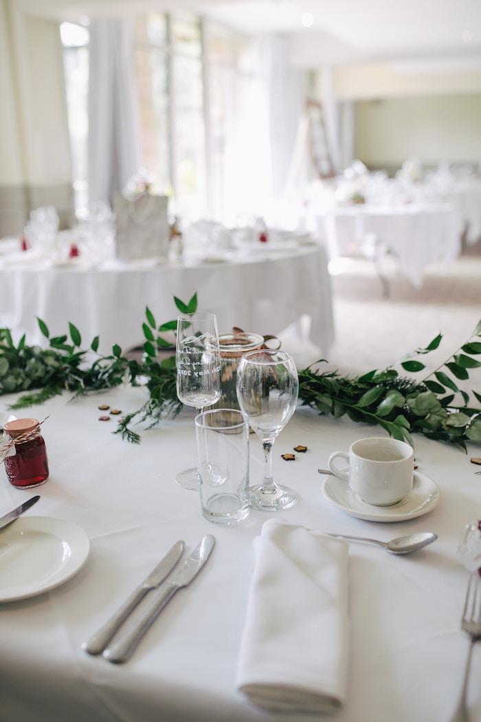 dressage de table pour un accueil officiel avec des couteaux tasse a cafe et soucoupe nappe blanche et plantes vertes
