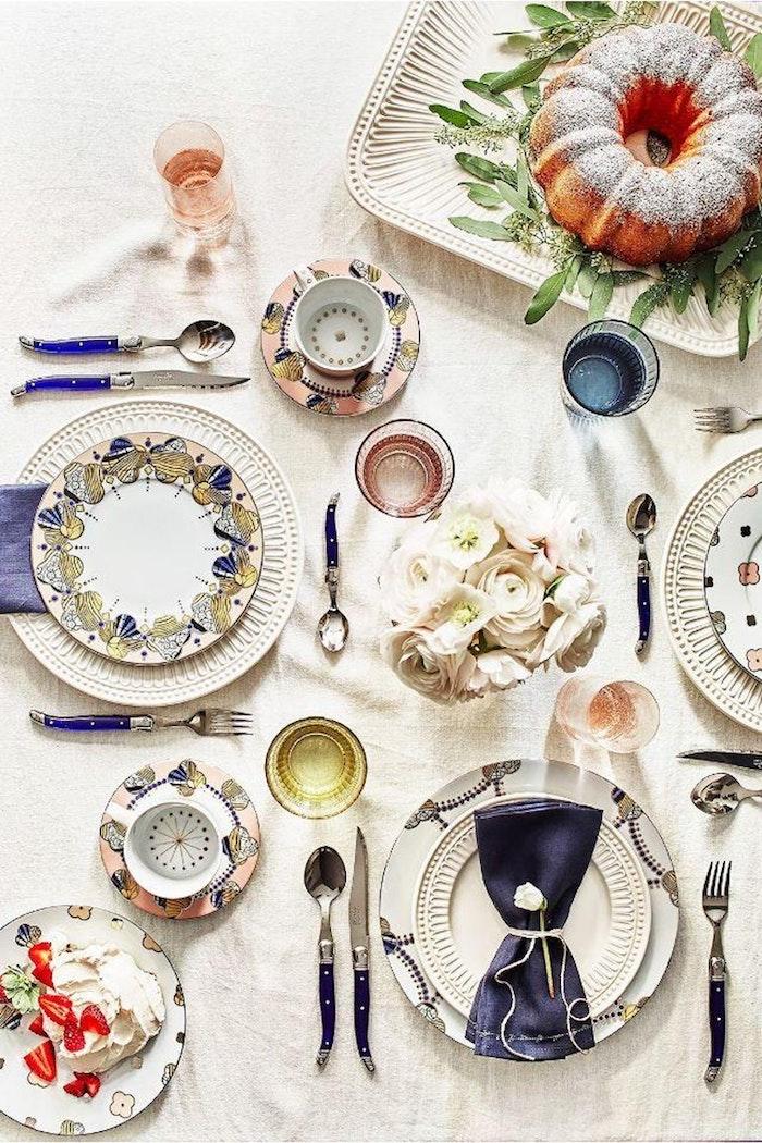 dresser une table a la francaise avec des assiettes multicolores en porcelaine bouquet de roses au centre de la table un cake saupodre dans un plateau garni des branches vertes