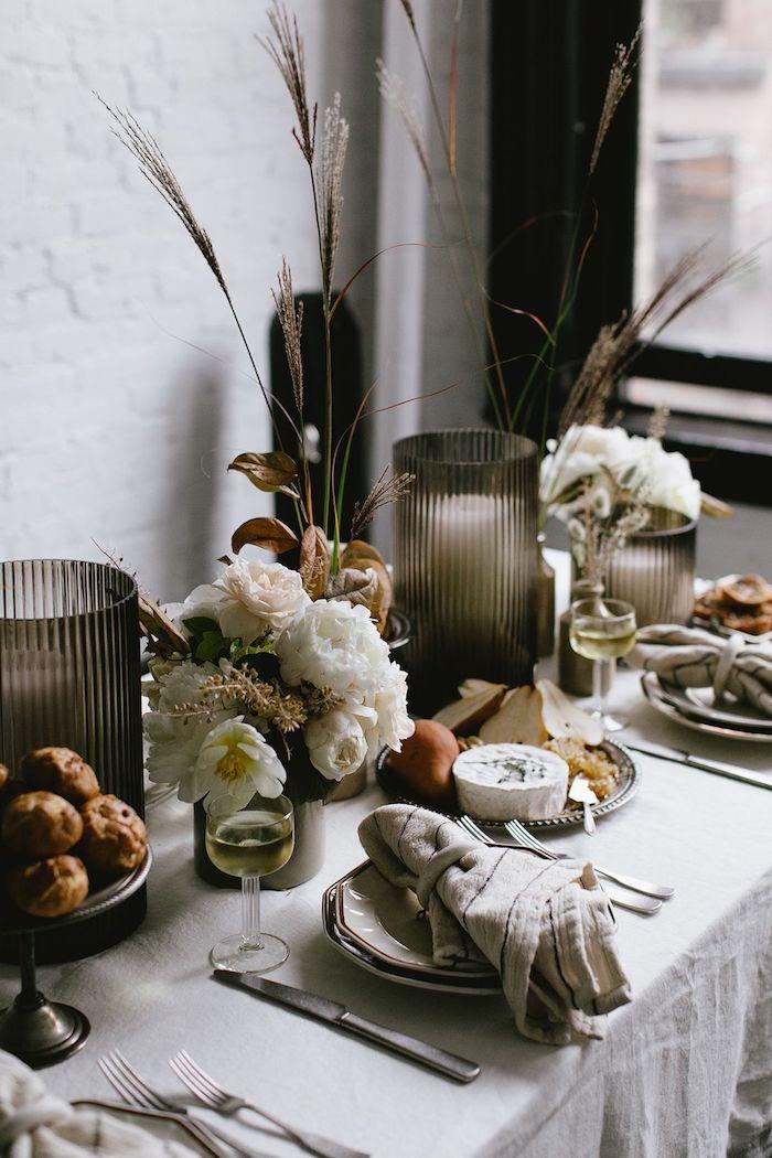 dresser une table en style automnale avec des fleurs blancs et des pommes grilles dqns des assiettes des ridaux noir et murs blanc