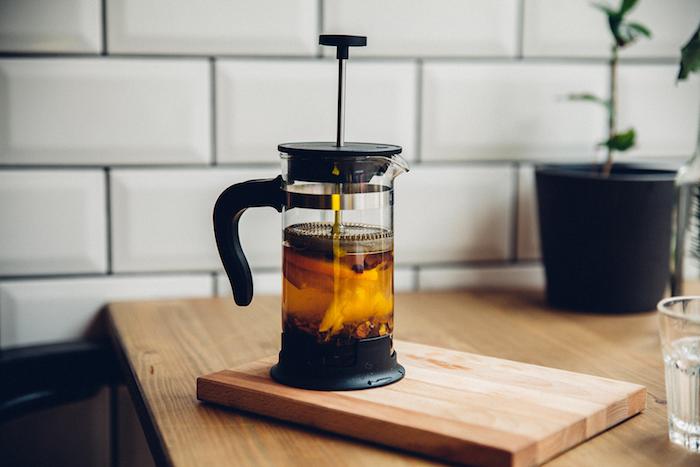 du cafe dans une cafeterie a piston sur une table en bois dans la cuisine en carrelage