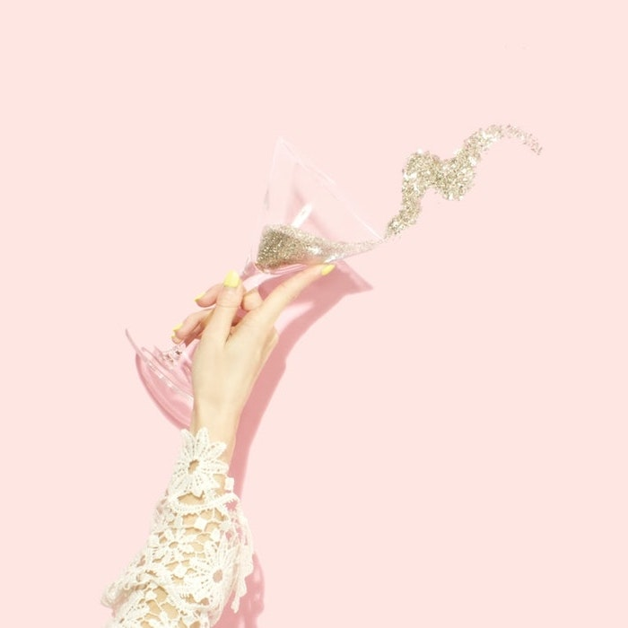 esthetique pastel pop une maine avec manche en broderie et une verre de champagne pleine de pailettes