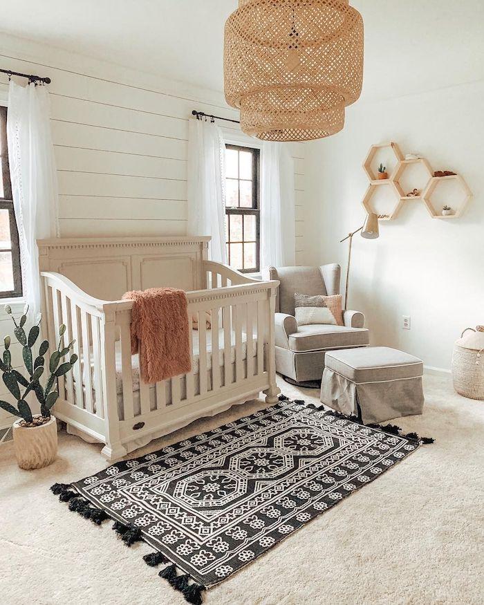 exemple chambre bébé nature avec cactus en pot lit bébé blanc fauteuil et repose pieds gris tapis noir et blanc murs blancs
