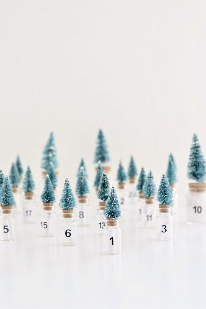 exemple de calendrier de l avent à remplir fioles de verre avec capuchons de liège surmontés de petits sapins decoratifs