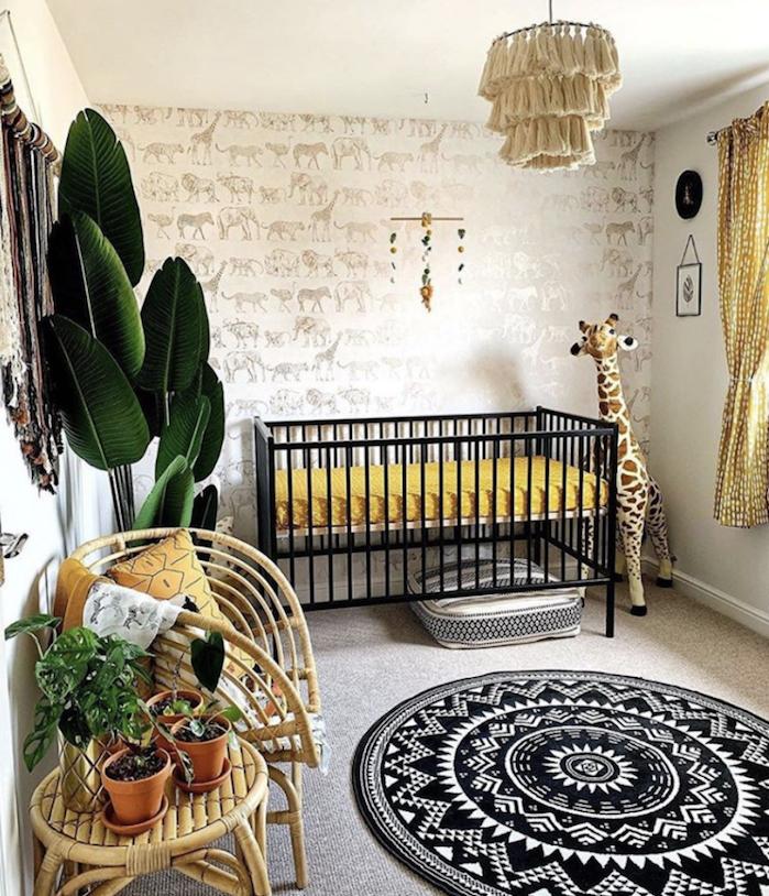exemple de chambre bébé nature avec lit metal noir tapis rond noir et blanc chaises tressées plante en pot vert mur tapissé de papier peint animal