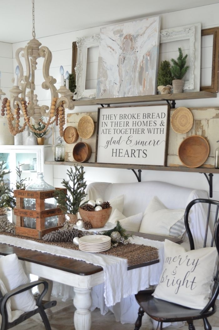 exemple de salon rustique d hiver avec canapé blanc table bois et blanc deco assiettes rotin et bois et des branches de pin lambris mural