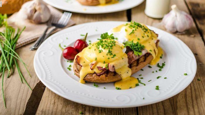 faire un brunch recette des oeufs benedicte servis avec de bacon et de sauce hollandaise dans uen assiette arrose de persil