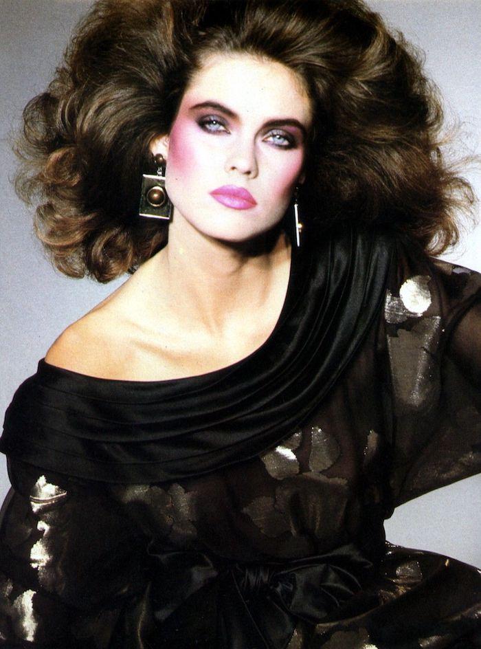 femme des années 80 vetue en noir avec du maquillage rose boucles d oreilles et cehveux bouffes