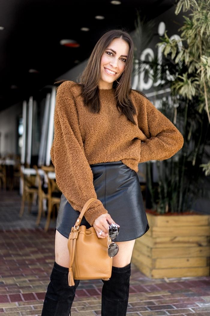 femme en mini jupe et bottes cuissardes velours noir pull oversize marron sac à main camel lunettes soleil