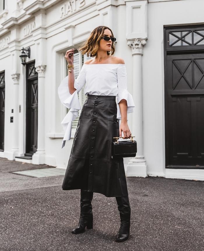 femme en mini jupe et bottes jupe longue cuir bottes cuissardes noires talons sac à main noir et or lunette soleil blouse blanche manche a effet