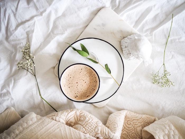 fond d ecran neutre et minimalistic avec une tasse de cafe au lit avec branches de plantes et des couettes