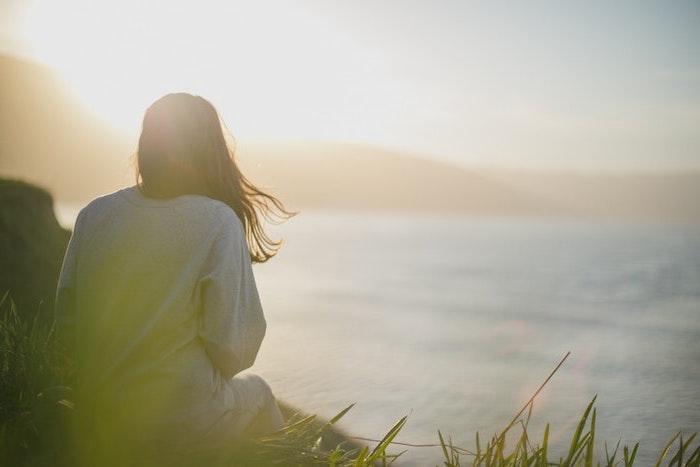 fond ecran aesthetic une fille assise sur l herbe regarde le soleil se couche au bord de la mer